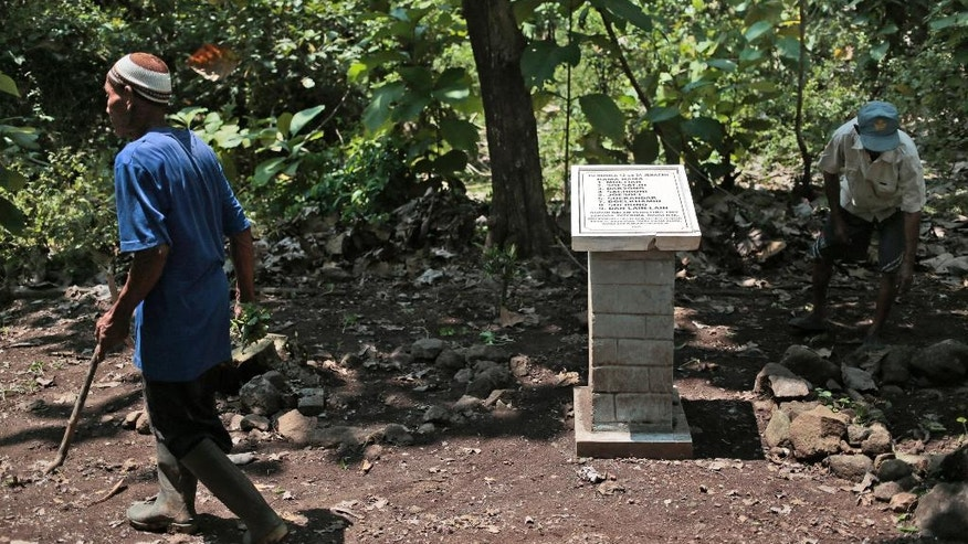 In this Sept. 3, 2016 photo, Asrori, left, and Sukar, eye witnesses to the aftermath of an execution of local communist party members in 1965, clean up dry leaves around the monument erected at the site of a mass grave in Plumbon village, Central Java, Indonesia. In a country pockmarked with hidden graves from one of the 20th century's worst mass killings, the village of Plumbon has something unique: a monument that names some of those believed killed when the nationwide bloodletting engulfed this hamlet half a century ago. (AP Photo/Dita Alangkara)