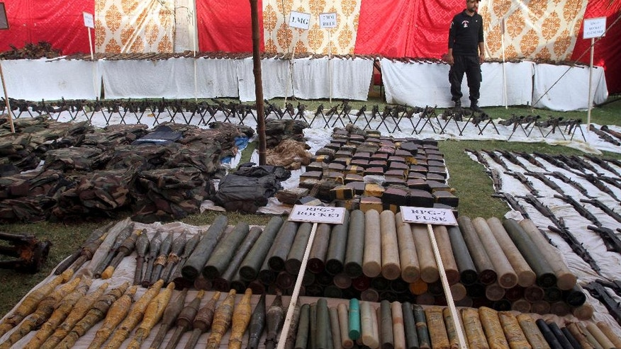 A Pakistani police commando stands beside the display of huge quantity of arms and ammunitions, which they said were seized during a raid on an abandoned house in Karachi, Pakistan, Wednesday, Oct. 5, 2016. Police seized a huge cache of arms and ammunitions, including anti-aircraft guns, sub-machine guns, light machine guns, rifles and rocket launchers during a raid in an abandoned house in the neighborhood of Pakistani port city Karachi, local media reported. (AP Photo/Fareed Khan)