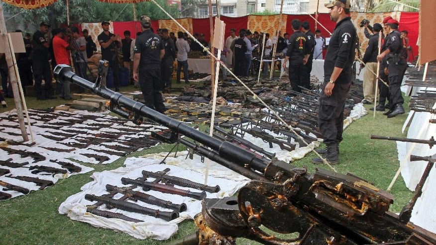 Pakistani police officers gather around the display of huge quantity of arms and ammunitions, which they said were seized during a raid on an abandoned house in Karachi, Pakistan, Wednesday, Oct. 5, 2016. Police seized a huge cache of arms and ammunitions, including anti-aircraft guns, sub-machine guns, light machine guns, rifles and rocket launchers during a raid in an abandoned house in the neighborhood of Pakistani port city Karachi, local media reported. (AP Photo/Fareed Khan)