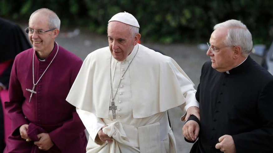 Pope Francis is flanked by Mons. Lorenzo Sapienza, right, and Archbishop of Canterbury, Justin Welby, as he arrives for vespers prayers in the church of San Gregorio al Celio, in Rome, Wednesday, Oct. 5, 2016. (AP Photo/Gregorio Borgia)