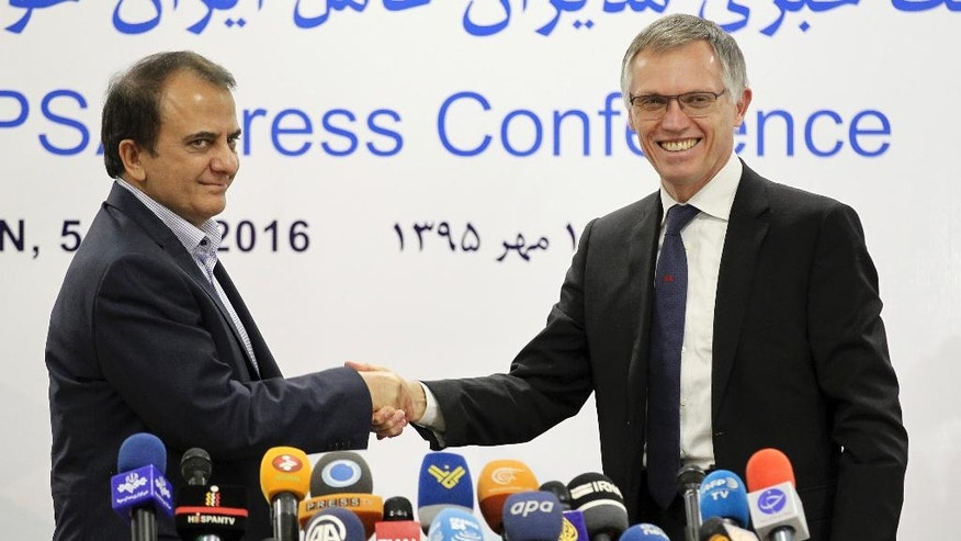 The managing director of Iranian car maker, Iran Khodro, Hashem Yekke Zare, left, and the chairman of the managing board at the French carmaker Peugeot Citroen PSA Carlos Tavares shake hands after a press conference in Tehran, Iran, Wednesday, Oct. 5, 2016. Peugeot Citroen PSA has reached a deal with Iran's biggest carmaker to open a plant producing 200,000 vehicles a year, renewing an old partnership with Iran Khodro Co following the lifting of international sanctions. The two companies showcased five models to be produced by IKAP, a joint venture first announced in January during a visit to France by Iranian President Hassan Rouhani. (AP Photo/Ebrahim Noroozi)
