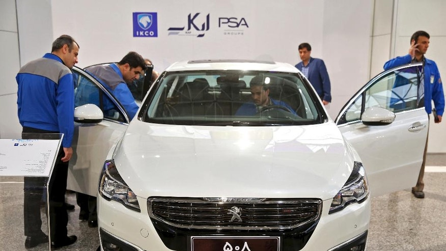 Workers inspect a Peugeot 508 at the Iran Khodro car factory in Tehran, Iran, Wednesday, Oct. 5, 2016. Peugeot Citroen PSA has reached a deal with Iran's biggest carmaker to open a plant producing 200,000 vehicles a year, renewing an old partnership with Iran Khodro Co following the lifting of international sanctions. The two companies showcased five models to be produced by IKAP, a joint venture first announced in January during a visit to France by Iranian President Hassan Rouhani. (AP Photo/Ebrahim Noroozi)