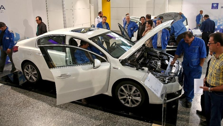 Iranian car workers inspect a Peugeot 508 at Iran Khodro car factory plant in Tehran, Iran, Wednesday, Oct. 5, 2016. Peugeot Citroen PSA has reached a deal with Iran's biggest carmaker to open a plant producing 200,000 vehicles a year, renewing an old partnership with Iran Khodro Co following the lifting of international sanctions. The two companies showcased five models to be produced by IKAP, a joint venture first announced in January during a visit to France by Iranian President Hassan Rouhani. (AP Photo/Ebrahim Noroozi)