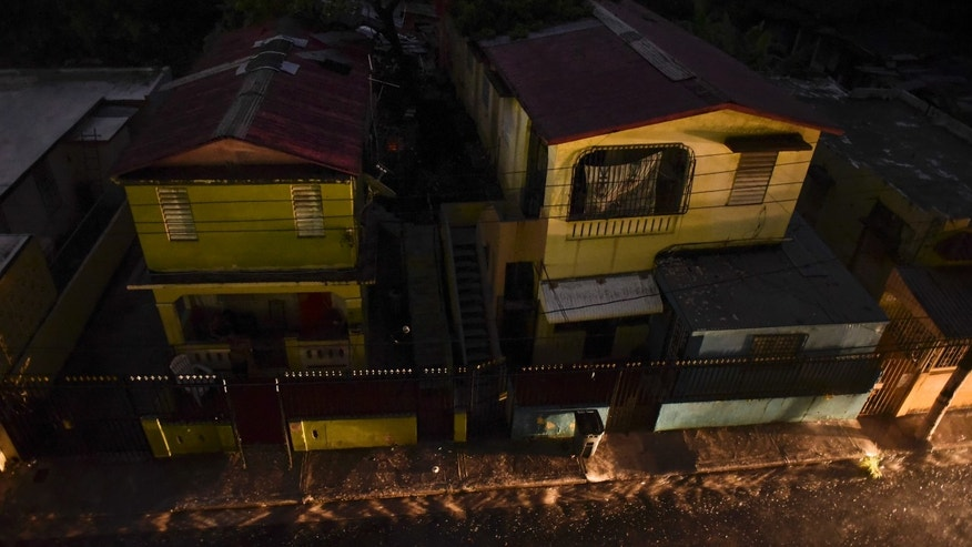 Vehicle lights illuminate a street after a massive blackout, in San Juan, Puerto Rico, Thursday, Sept. 22, 2016. Puerto Ricans faced another night of darkness Thursday as crews slowly restored electricity a day after a fire at a power plant caused the aging utility grid to fail and blacked out the entire island. (AP Photo/Carlos Giusti)