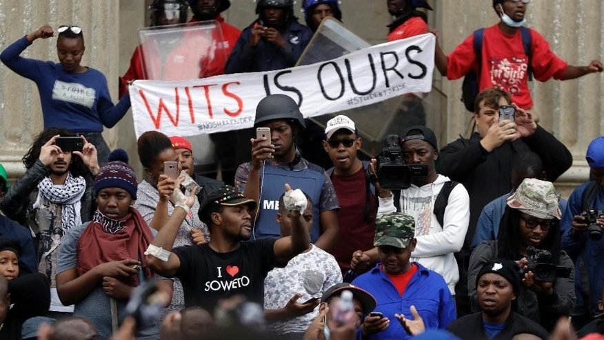FILE - In this Oct. 4, 2016, file photo, a protester, centre left, addresses fellow students outside the Great Hall at the University of the Witwatersrand in Johannesburg, South Africa. In a racially charged scene, a mostly black group of student protesters on Wednesday confronted white students who want protests for free education to stop so they can complete the academic year. (AP Photo/Themba Hadebe, File)