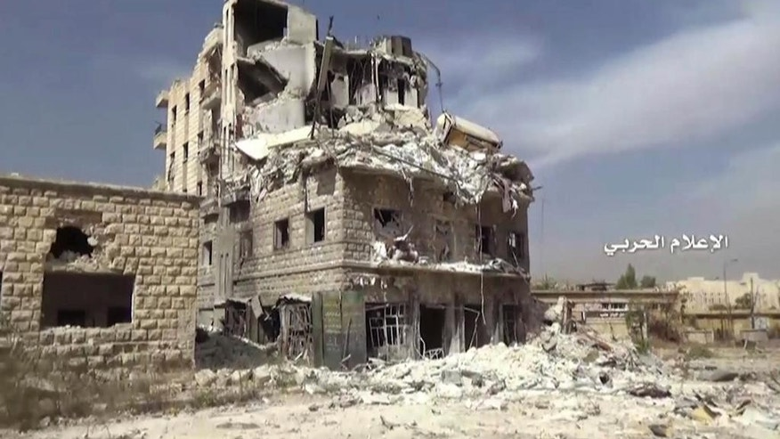 In this still image taken from video provided by the Syrian government-controlled Syrian Central Military Media, damaged buildings inside the Bustan Al-Basha neighborhood of Aleppo, Syria on Tuesday, Oct. 4, 2016.  The footage shows extensive destruction to buildings in the neighborhood and a factory of hand-made bombs using home gas bottles as shells. (Syrian Central Military Media via AP)