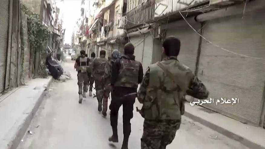 In this still image taken from video provided by the Syrian government-controlled Syrian Central Military Media, government troops patrol inside the Bustan Al-Basha neighborhood of Aleppo, Syria on Tuesday, Oct. 4, 2016.  The footage shows extensive destruction to buildings in the neighborhood and a factory of hand-made bombs using home gas bottles as shells. (Syrian Central Military Media via AP)