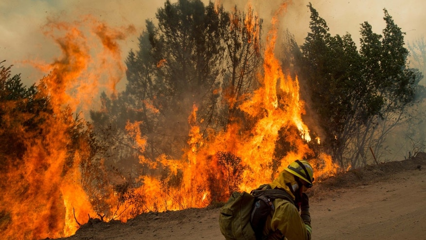 A firefighter covers his face while battling a wildfire near Morgan Hill, Calif., Tuesday, Sept. 27, 2016. The grass fire along a Northern California highway spread to parched trees, and flying embers landed on nearby homes, setting at least eight homes on fire, authorities said. (AP Photo/Noah Berger)