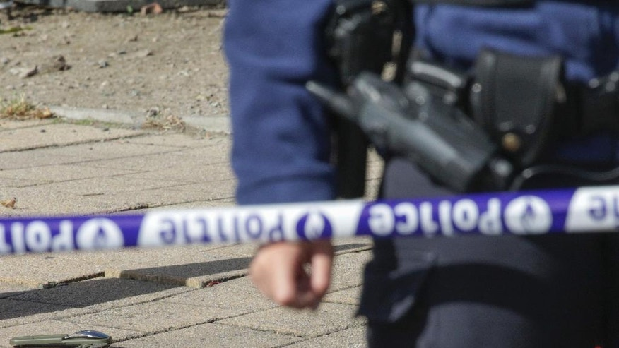 An officer stands next to the scene where an unidentified man stabbed two police officers, in the Schaerbeek neighborhood in Brussels, Wednesday, Oct. 5, 2016. The man stabbed one officer in the neck and the other in the abdomen and then fled the scene in an incident that Belgian prosecutors say could be terror-related. (AP Photo/Olivier Matthys)
