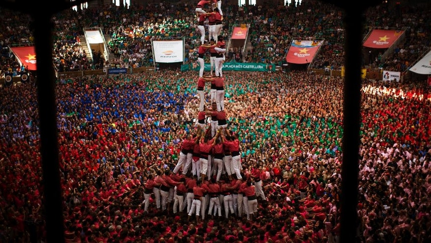 "FILE - In this Sunday, Oct. 2, 2016 file photo, members of ""Vella de Xiquets de Valls"" form their human tower during the 26th Human Tower Competition in Tarragona, Spain. The tradition of building human towers, or Castells, dates back to the 18th century and takes place during festivals in Catalonia. ""Colles,"" or teams, compete to build the tallest and most complicated towers. The structure of the castells varies depending on their complexity. (AP Photo/Emilio Morenatti, File)"