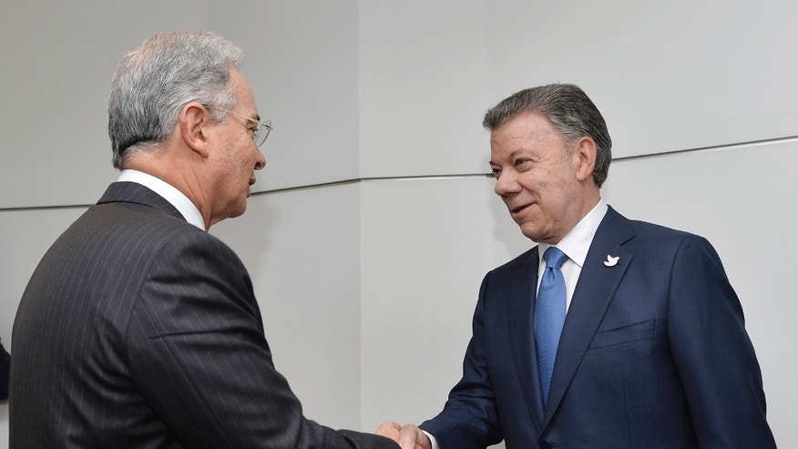 Senator and ex-President Alvaro Uribe shakes hands with President Juan Manuel Santos on Oct. 5, 2016.
