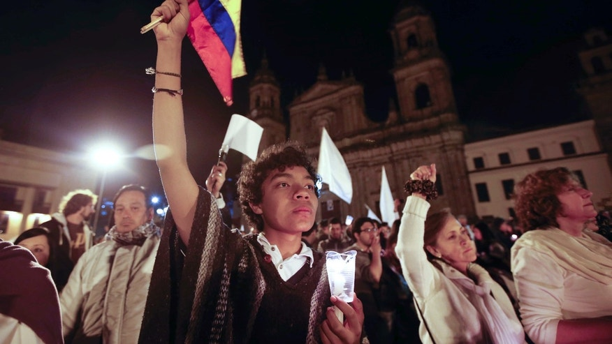 A youth holds a Colombian flag during a rally for peace in Bogota, Colombia, Wednesday, Oct. 5, 2016.