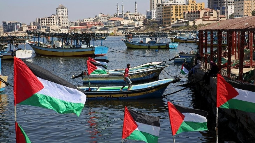 A Palestinian walks on a boat decorated with national flags as they await the arrival of an international boat trying to break Israel's blockade of the Gaza Strip, at the fishermen port in Gaza City, Thursday, Oct. 6, 2016. A boat carrying 13 pro-Palestinian female activists was escorted to shore and docked at an Israeli port on Thursday after being intercepted by the navy while trying to break Israel's blockade of the Gaza Strip, the Israeli military said. (AP Photo/Adel Hana)