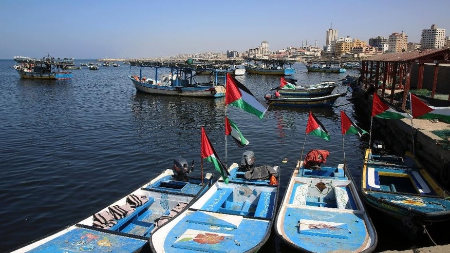 Fishing boats, decorated with national flags, await the arrival of an international boat trying to break Israel's blockade of the Gaza Strip, at the fishermen port in Gaza City, Thursday, Oct. 6, 2016. A boat carrying 13 pro-Palestinian female activists was escorted to shore and docked at the Israeli port of Ashod on Thursday after being intercepted by the navy while trying to break Israel's blockade of the Gaza Strip, the Israeli military said. (AP Photo/Adel Hana)