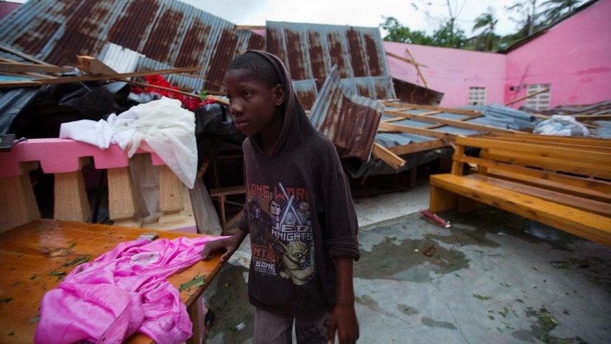 A boy stands inside a church after it was damaged by Hurricane Matthew in Saint-Louis, Haiti, Wednesday, Oct. 5, 2016.  Rescue workers in Haiti struggled to reach cutoff towns and learn the full extent of the death and destruction caused by Hurricane Matthew as the storm began battering the Bahamas on Wednesday and triggered large-scale evacuations along the U.S. East Coast. ( AP Photo/Dieu Nalio Chery)