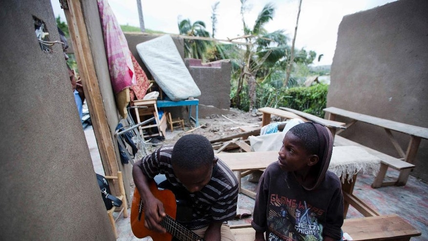 A man sits inside of what is left of his home with his cousin after it was damaged by Hurricane Matthew in Saint-Louis, Haiti, Wednesday, Oct. 5, 2016.  Rescue workers in Haiti struggled to reach cutoff towns and learn the full extent of the death and destruction caused by Hurricane Matthew as the storm began battering the Bahamas on Wednesday and triggered large-scale evacuations along the U.S. East Coast. ( AP Photo/Dieu Nalio Chery)