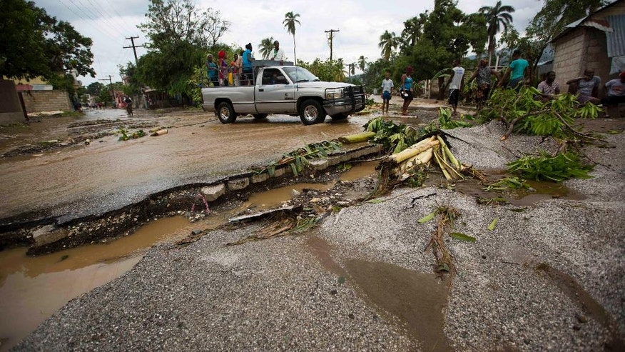 A truck negotiates a road damaged by Hurricane Matthew, in Petit Goave, Haiti, Wednesday, Oct. 5, 2016. Rescue workers in Haiti struggled to reach cutoff towns and learn the full extent of the death and destruction caused by Hurricane Matthew as the storm began battering the Bahamas on Wednesday and triggered large-scale evacuations along the U.S. East Coast. ( AP Photo/Dieu Nalio Chery)