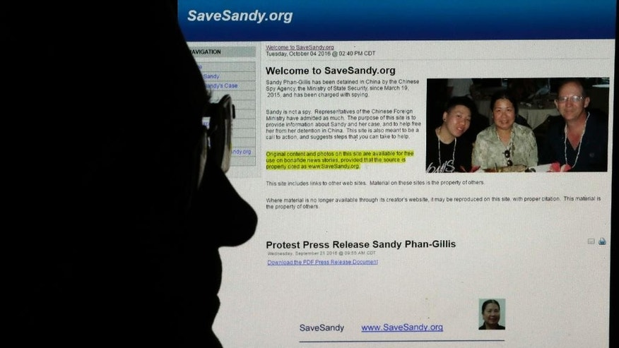 "In this Oct. 4, 2016, photo, Jeff Gillis sits in front of a computer screen showing the SaveSandy.org website in Houston, Texas.  The husband of U.S. citizen Phan ""Sandy"" Phan-Gillis, who has been charged in China with spying, has spent months trying to prove his wife's innocence with the little information he had. He has collected documents and letters that he hopes can be used as evidence for her defense.  (AP Photo/David J. Phillip)"