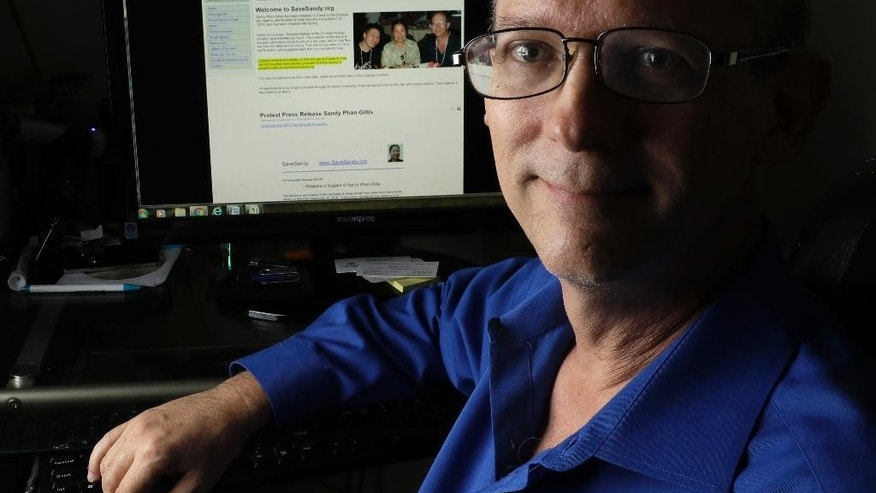 "In this Oct. 4, 2016, photo, Jeff Gillis sits in front of a computer displaying a website supporting his wife's release in Houston, Texas.  The husband of U.S. citizen Phan ""Sandy"" Phan-Gillis, who has been charged in China with spying, has spent months trying to prove his wife's innocence with the little information he had. He has collected documents and letters that he hopes can be used as evidence for her defense.  (AP Photo/David J. Phillip)"