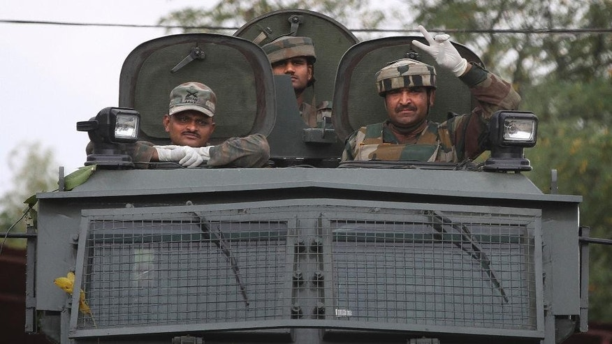 An Indian Army soldier shows a victory sign with others on top of their armored vehicle outside their base camp in Langate 75 kilometres (47 miles) north of Srinagar, Indian controlled Kashmir, India, Thursday, Oct 6, 2016. The Indian army says soldiers foiled an attack on an army camp and killed three suspected rebels in Indian-controlled Kashmir. (AP Photo/Mukhtar Khan)