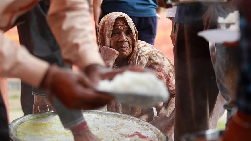 An Indian woman waits to receive food at a relief camp set up inside a government-run school after residents living close to the highly militarized Line of Control dividing Kashmir between India and Pakistan were evacuated to a safer place, at Domana village, on the outskirts of Jammu, India, Wednesday, Oct. 5, 2016. The villagers are familiar with the drill, though evacuations have been rare since tension along the border declined dramatically following a 2003 India-Pakistan cease-fire accord. (AP Photo/Channi Anand)