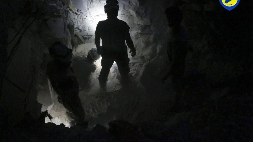 This Tuesday, Oct. 4, 2016 photo, provided by the Syrian Civil Defense group known as the White Helmets, shows Civil Defense workers from the White Helmets digging in the rubles to remove bodies and look for survivors, after airstrikes hit Bustan al-Basha neighborhood in Aleppo, Syria. The U.N. on Wednesday released stark satellite images showing the most recent destruction of Syria's embattled northern city of Aleppo, pounded by Syrian and Russian airstrikes since the collapse of a U.S.-Russia brokered cease-fire two weeks ago. (Syrian Civil Defense White Helmets via AP)