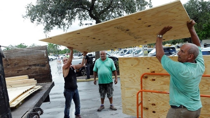 Jose Luis and Miro Espana load plywood into a truck in preparation for Hurricane Matthew on Oct. 5, 2016, in Miami.