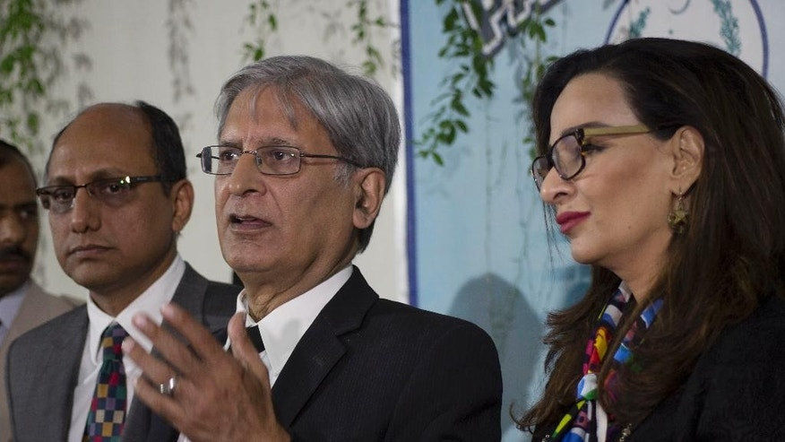 "Pakistani lawmaker from the People's party who moved the bill against honor killing, Aitzaz Ahsan, center, addresses media at the Parliament in Islamabad, Pakistan, Thursday, Oct. 6, 2016.  Pakistani lawmakers have passed a law that stiffens the penalty for convicted ""honor"" killers and closes a loophole that often allowed them to go free. The law gives a mandatory 25 years in prison to anyone convicted of killing in the name of honor and no longer allows family members to forgive the killers. (AP Photo/B.K. Bangash)"