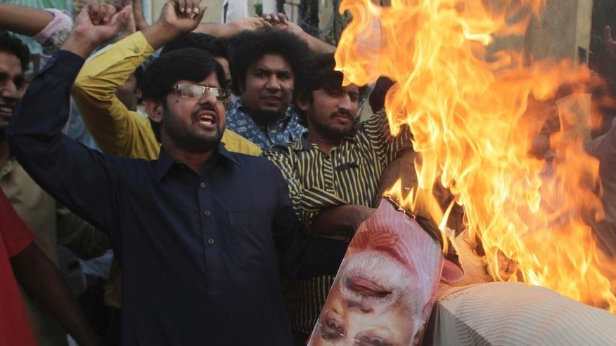 Pakistani protesters burn an effigy of Indian Prime Minister Narendra Modi at a rally in Lahore, Pakistan, Thursday, Oct. 6, 2016. Pakistan's powerful army chief lashed out at India Thursday, warning that any act of aggression from New Delhi would not go unpunished as tensions spike between the two countries over the divided region of Kashmir. (AP Photo/K.M. Chaudary)