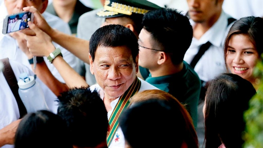 FILE - In this Tuesday, Oct. 4, 2016 file photo, Philippine President Rodrigo Duterte, center, is greeted by supporters following his visit to the headquarters of the Philippine Army in suburban Taguig city, east of Manila, Philippines. An independent poll released Thursday, Oct. 6, showed that more than three-quarters of Filipinos are satisfied with President Rodrigo Duterte, even though he is under fire internationally for his deadly crackdown on suspected drug dealers and users. The survey, conducted by Social Weather Stations from Sept. 24 to Sept. 27 and published Thursday. (AP Photo/Bullit Marquez, File)
