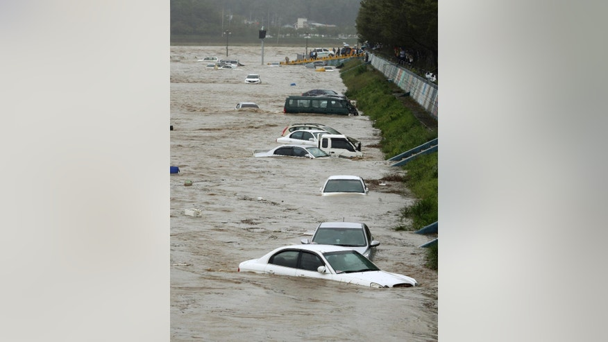 Vehicles are submerged in floodwaters caused by Typhoon Chaba in Gyeongju, South Korea, Wednesday, Oct. 5, 2016. Typhoon Chaba slammed South Korea on Wednesday, bringing heavy rains and raging waves to Jeju Island, an island south of the mainland, and the country's southern cities. (Kim Jun-bum/Yonhap via AP)