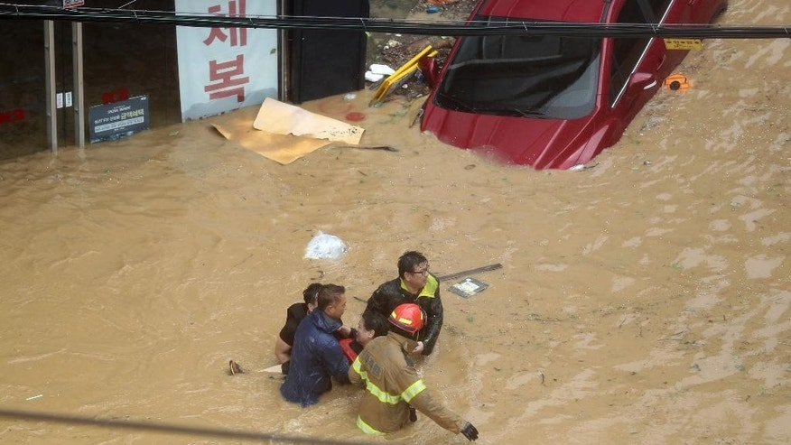 Rescue workers carry a resident through a flooded street caused by Typhoon Chaba in Ulsan, South Korea, Wednesday, Oct. 5, 2016. Typhoon Chaba slammed South Korea on Wednesday, bringing heavy rains and raging waves to Jeju Island, an island south of the mainland, and the country's southern cities. (Lee Sang-hyun/Yonhap via AP)