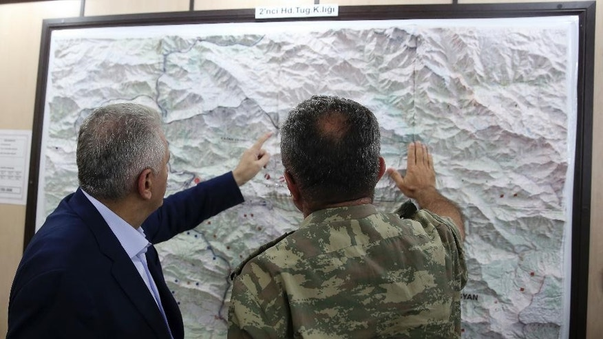 "FILE - In this Monday, Sept. 5, 2016 photo, an army commander informs Turkey's Prime Minister Binali Yildirim, left, on a Turkey-Iraq border map, in Cukurca, Turkey. Iraq's Foreign Ministry has summoned Turkeys' ambassador to Baghdad over ""provocative"" comments by Turkish Prime Minister Binali Yildirim about the planned operation to dislodge Islamic State militants from the city of Mosul. (Prime Ministry Press Service, Pool photo via AP, File)"