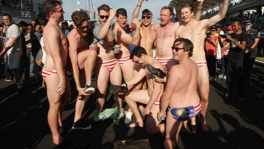 In this Sunday, Oct. 2, 2016 photo, Australian men celebrate in Budgy Smuggler-brand swimsuits decorated with the Malaysian flag at the conclusion of the Malaysian Formula One Grand Prix in Sepang, Malaysia. Malaysian authorities who have detained nine Australian men for three nights would regard their actions in stripping down to their briefs and drinking beer from shoes as premeditated, Australia's foreign minister said Wednesday, Oct. 5, 2016. (AP Photo)