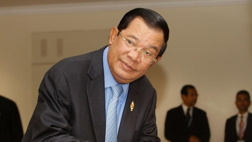Cambodia's Prime Minister Hun Sen looks on as he registers his name before a parliament session, in Phnom Penh, Cambodia, Friday, Oct. 7, 2016.  The main opposition party of Cambodia National Rescue Party (CNRP) on Friday boycotted a parliament session due to their lawmaker members's security, as its calls on the authorities to protect the safety of opposition MPs, according to CNRP press conference. (AP Photo/Heng Sinith)