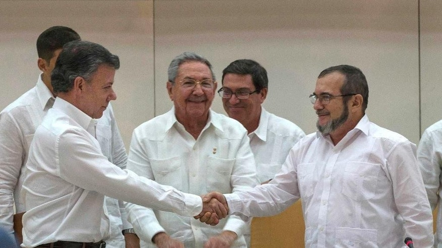 "FILE - In this Wednesday, Sept. 23, 2015 file photo Cuba's President Raul Castro, center, smiles as Colombian President Juan Manuel Santos, left, and Commander the Revolutionary Armed Forces of Colombia or FARC, Timoleon Jimenez, known as ""Timochenko"",  shake hands, in Havana, Cuba. Colombian President Juan Manuel Santos has won Nobel Peace Prize it was announced on Friday Oct. 7, 2016. (AP Photo/Ramon Espinosa, File)"