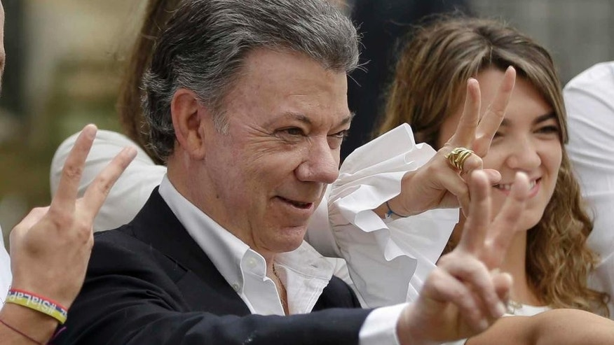 FILE - In this Sunday, Oct. 2, 2016 file photo Colombia's President Juan Manuel Santos makes the victory sign after voting in a referendum to decide whether or not to support the peace deal he signed with rebels of the Revolutionary Armed Forces of Colombia, FARC, in Bogota, Colombia. Colombian President Juan Manuel Santos has won Nobel Peace Prize it was announced on Friday Oct. 7, 2016. (AP Photo/Ricardo Mazalan, File)