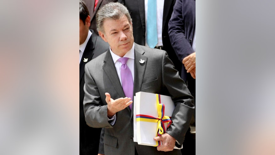FILE - In this Thursday, Aug. 25, 2016 file photo Colombia's President Juan Manuel Santos holds the peace deal with rebels of the Revolutionary Armed Forces of Colombia, FARC after delivering it to Congress in Bogota, Colombia. Colombian President Juan Manuel Santos has won Nobel Peace Prize it was announced on Friday Oct. 7, 2016.  (AP Photo/Felipe Caicedo, File)