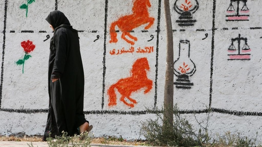 "A Moroccan woman walks past electoral paintings representing a political party logos for the upcoming municipal elections in Casablanca, Morocco, Wednesday, Oct. 5, 2016. Party logos are, from left, are, ""Socialist Union of the People's Forces"" (Rose), Constitutional Union (horse), ""Justice and Development Party"" (Lamp) and Party of Istiqlal (Scale) at the Sidi Othmane district of Casablanca. To help illiterate people vote, only party logos will appear on ballot papers, and the numbers seen in the image are allocated to each party for displaying purposes only during the campaign. Elections are scheduled Friday 7. (AP Photo/Abdeljalil Bounhar)"