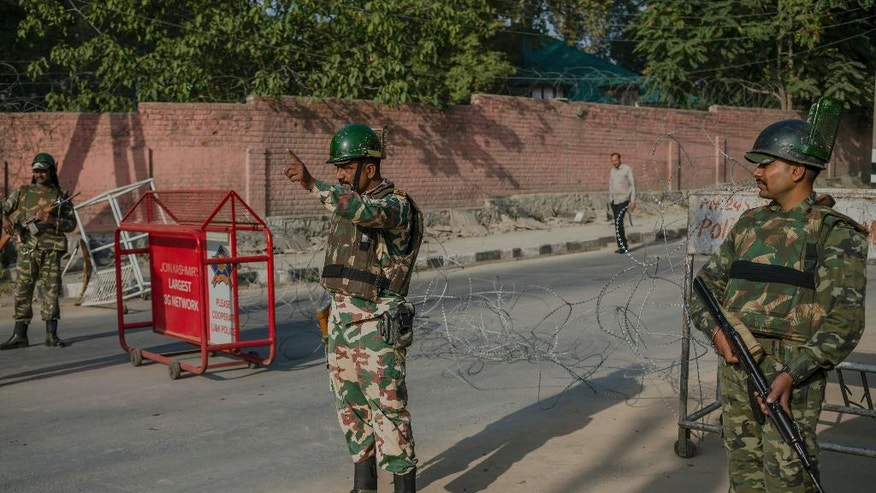 An Indian paramilitary soldier, center, orders a Kashmiri civilian to turn back at a temporary checkpoint during curfew in Srinagar, Indian-controlled Kashmir, Friday, Oct. 7, 2016. Authorities imposed a curfew in many parts of the Indian-controlled Kashmir to prevent a protest march to the disputed Himalayan region's office of United Nations Military Observer Group in India and Pakistan (UNMOGIP) called by separatist leaders seeking end of Indian rule. (AP Photo/Dar Yasin)