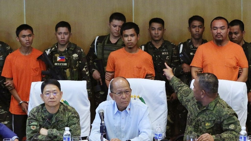 Philippine military chief Gen. Ricardo Visaya, right, points at suspected Muslim extremists, from left in orange shirts, Wendel Apostol Facturan, Musali Mustapha and TJ Tagdaya Macabalang, as they are presented to reporters at Camp Aguinaldo military headquarters in Quezon city, north of Manila, Philippines Friday, Oct. 7, 2016. Philippine troops have captured the three suspects in the bombing of a night market that killed 15 people and seized a cellphone video of the blast from them that they apparently took for propaganda purposes, the defense chief said Friday. Also in photo are, Philippine Army Commanding General Lt. Gen. Eduardo Ano, seated left, and Philippine Defense Secretary Delfin Lorenzana, seated center. (AP Photo/Aaron Favila)