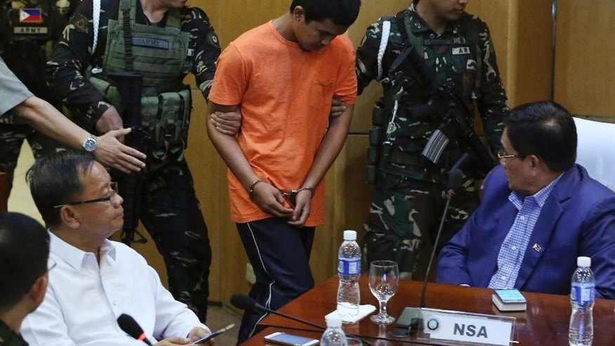 Suspected Muslim extremist Musali Mustapha is escorted inside a room as he and two other suspects are presented to reporters at Camp Aguinaldo military headquarters in Quezon city, north of Manila, Philippines Friday, Oct. 7, 2016. Philippine troops have captured three suspects in the bombing of a night market that killed 15 people and seized a cellphone video of the blast from them that they apparently took for propaganda purposes, the defense chief said Friday. (AP Photo/Aaron Favila)