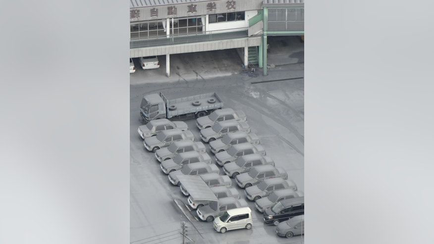 This aerial photo shows cars totally covered by gray ash parked on the compound of a driving school in Aso, Kumamoto Prefecture, southern Japan, Saturday morning, Oct. 8, 2016, following Mount Aso erupted earlier in the day. Mount Aso has sent huge plumes of gray smoke as high as 11 kilometers (6.8 miles) into the air in one of the volcano's biggest explosions in years. (Hiroko Harima/Kyodo News via AP)