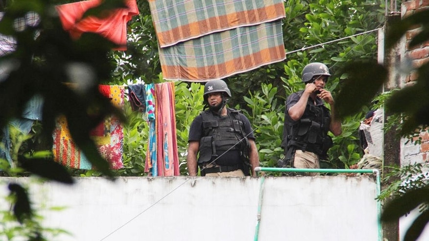 Bangladesh's Special Weapons and Tactics (SWAT) policemen keep a watch from a rooftop after a raid in Gazipur, Bangladesh, Saturday, Oct. 8, 2016. Security forces in Bangladesh killed more than 10 suspected militants in three separate raids Saturday in an ongoing crackdown against Islamic extremism in the South Asian nation, a top government official said. The suspects were members of the banned group Jumatul Mujahedeen Bangladesh, or JMB, which the government has blamed for a deadly attack in July at a restaurant in Dhaka, the capital, said Home Minister Asaduzzaman Khan. (AP Photo)