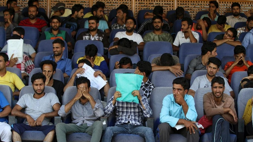 In this Thursday, Sept. 29, 2016 photo, young Kashmiris cover their faces during a police recruitment drive in Srinagar, Indian controlled Kashmir. Some 20,000 young people who are trying out for 8,000 jobs advertised by the state police, in the troubled Himalayan region that is wracked by rampant unemployment. But being a policeman in Indian-controlled Kashmir is both shameful and dangerous, a place where anti-India sentiments are high. Most candidates hid their faces from the photographers covering the recruitment event, highlighting the discomfort Kashmiri police face in their work. (AP Photo/Mukhtar Khan)
