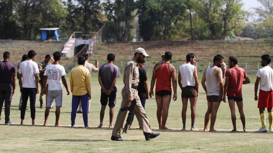In this Thursday, Sept. 29, 2016 photo, a policeman walks past young Kashmiris attending a physical fitness test during a police recruitment drive in Srinagar, Indian controlled Kashmir. Some 20,000 young people who are trying out for 8,000 jobs advertised by the state police, in the troubled Himalayan region that is wracked by rampant unemployment. But being a policeman in Indian-controlled Kashmir is both shameful and dangerous, a place where anti-India sentiments are high. Most candidates hid their faces from the photographers covering the recruitment event, highlighting the discomfort Kashmiri police face in their work. (AP Photo/Mukhtar Khan)