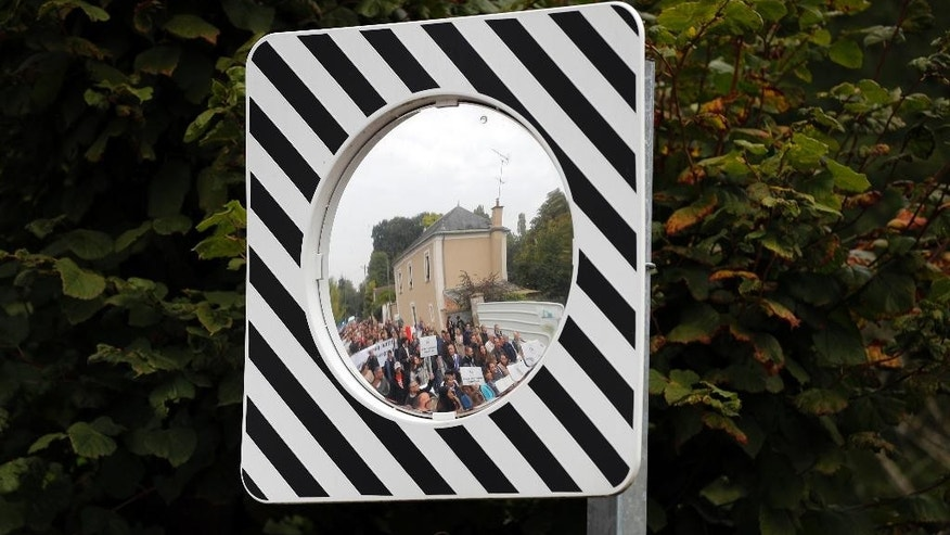 Local residents are reflected in a mirror as they demonstrate in Forges-les-Bains, south of Paris, France, Saturday, Oct. 8, 2016. French villagers are protesting the arrival of migrants who are being spread out around the country as the government shuts down the slum-like camp in Calais that has become a flashpoint in Europe's migrant crisis. (AP Photo/Christophe Ena)