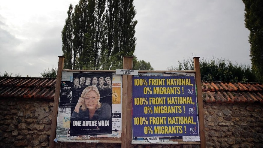 An electoral board showing France's far-right National Front president Marine Le Pen and reading: 100% National Front. 0% migrants is pictured during a demonstration  in Forges-les-Bains, south of Paris, France, Saturday, Oct. 8, 2016. French villagers are protesting the arrival of migrants who are being spread out around the country as the government shuts down the slum-like camp in Calais that has become a flashpoint in Europe's migrant crisis. (AP Photo/Christophe Ena)