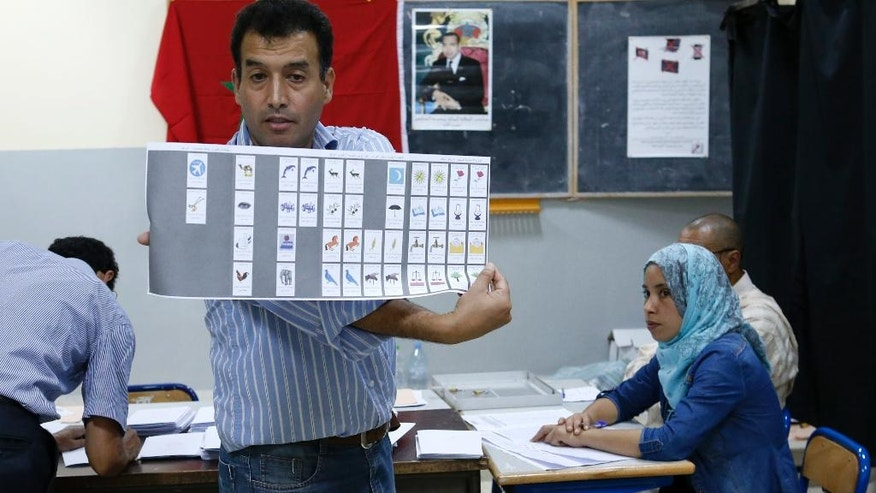 A polling station staff shows a ballot as officials and political party's representatives count the ballots in a polling station in Rabat, Morocco, Friday,in Rabat, Morocco, Friday, Oct. 7, 2016.  Amid worries about jobs and extremism, millions of Moroccans voted Friday in parliamentary elections that will determine whether moderate Islamists will keep control of the government or lose power to a young rival party close to the powerful royal palace. (AP Photo/Abdeljalil Bounhar)