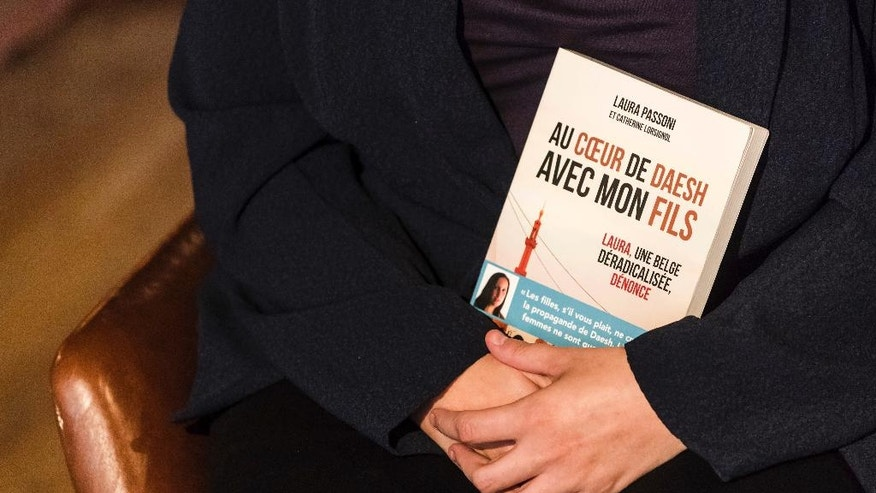 Laura Passoni holds her book as she talks during an interview with the Associated Press in an hotel in Brussels on Thursday, Oct. 6, 2016. Passoni, a Belgian woman who joined Islamic State with her 4-year-old son and later escaped has written a book geared to dissuade young people tempted to follow the same path. (AP Photo/Geert Vanden Wijngaert)